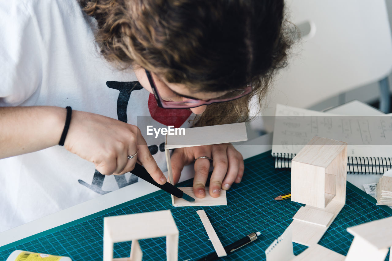 Close-up of young woman working with cardboard on table