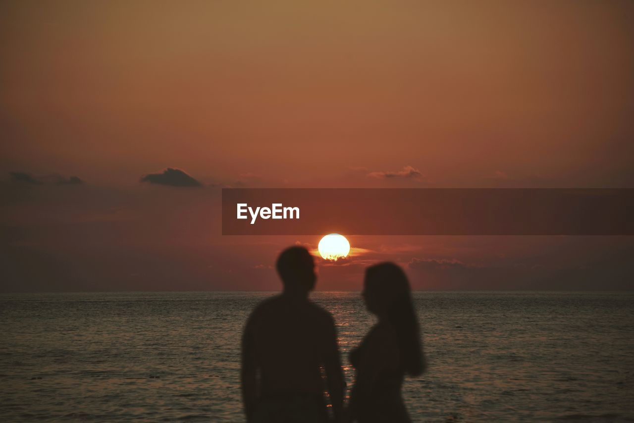 sky, sunset, water, two people, sea, scenics - nature, beauty in nature, togetherness, bonding, horizon over water, sun, real people, silhouette, lifestyles, tranquil scene, horizon, orange color, tranquility, positive emotion, couple - relationship, outdoors