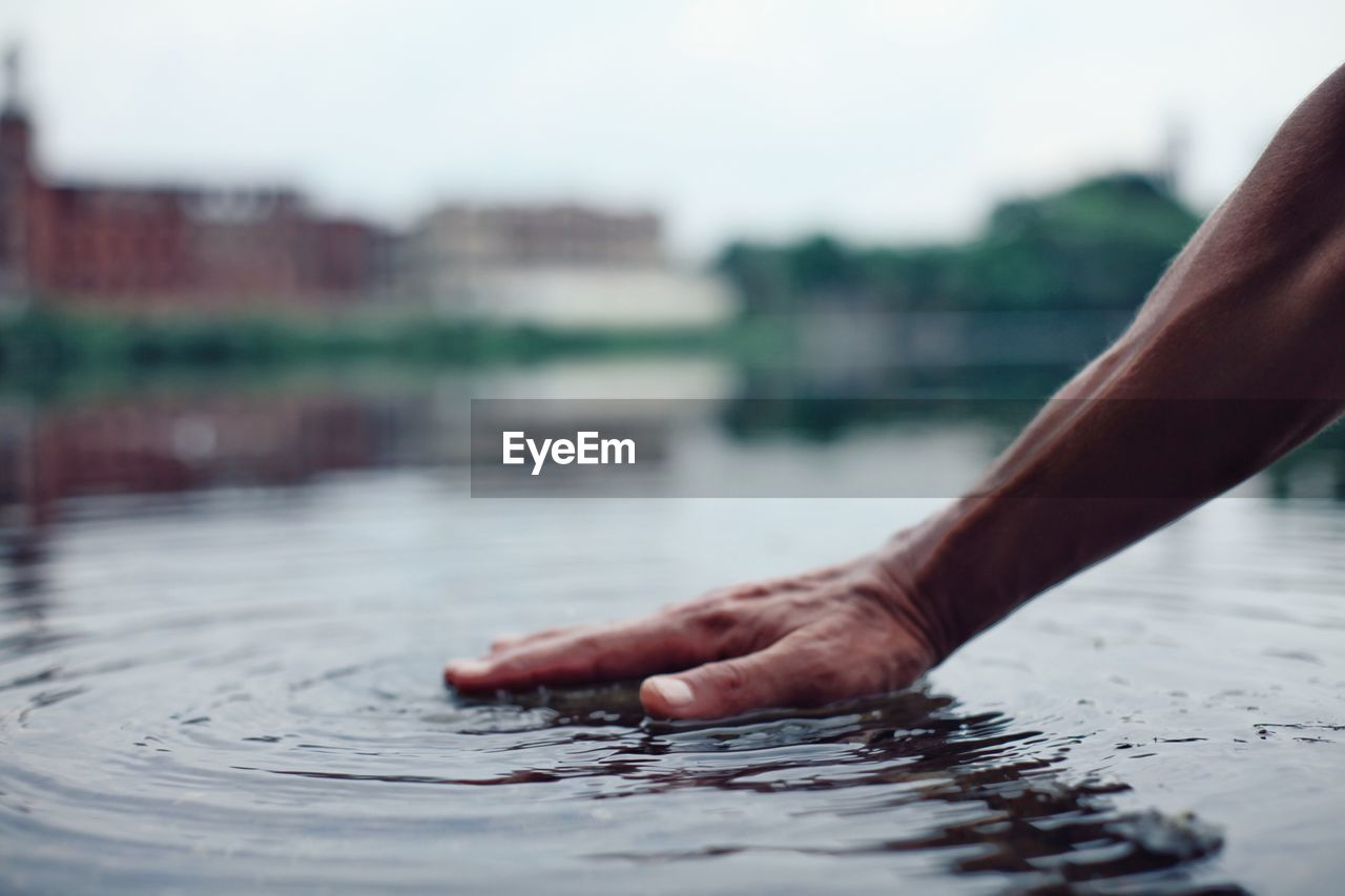 Cropped Image Of Person Touching Water In River