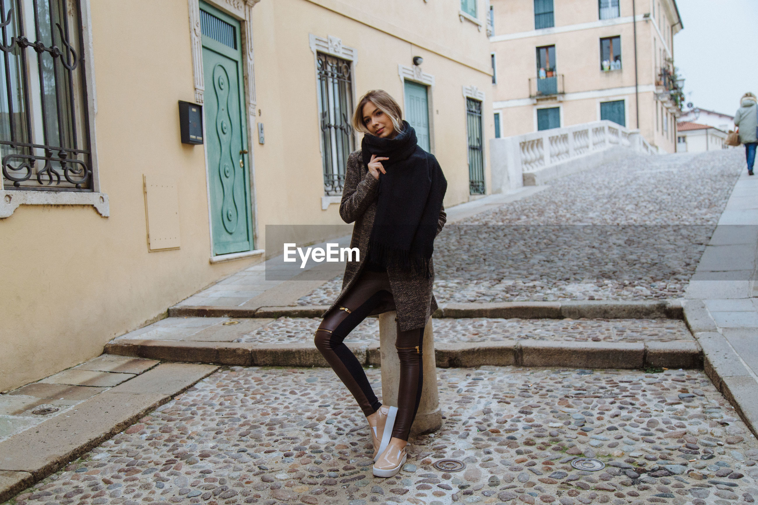 Woman sitting on bollard in city