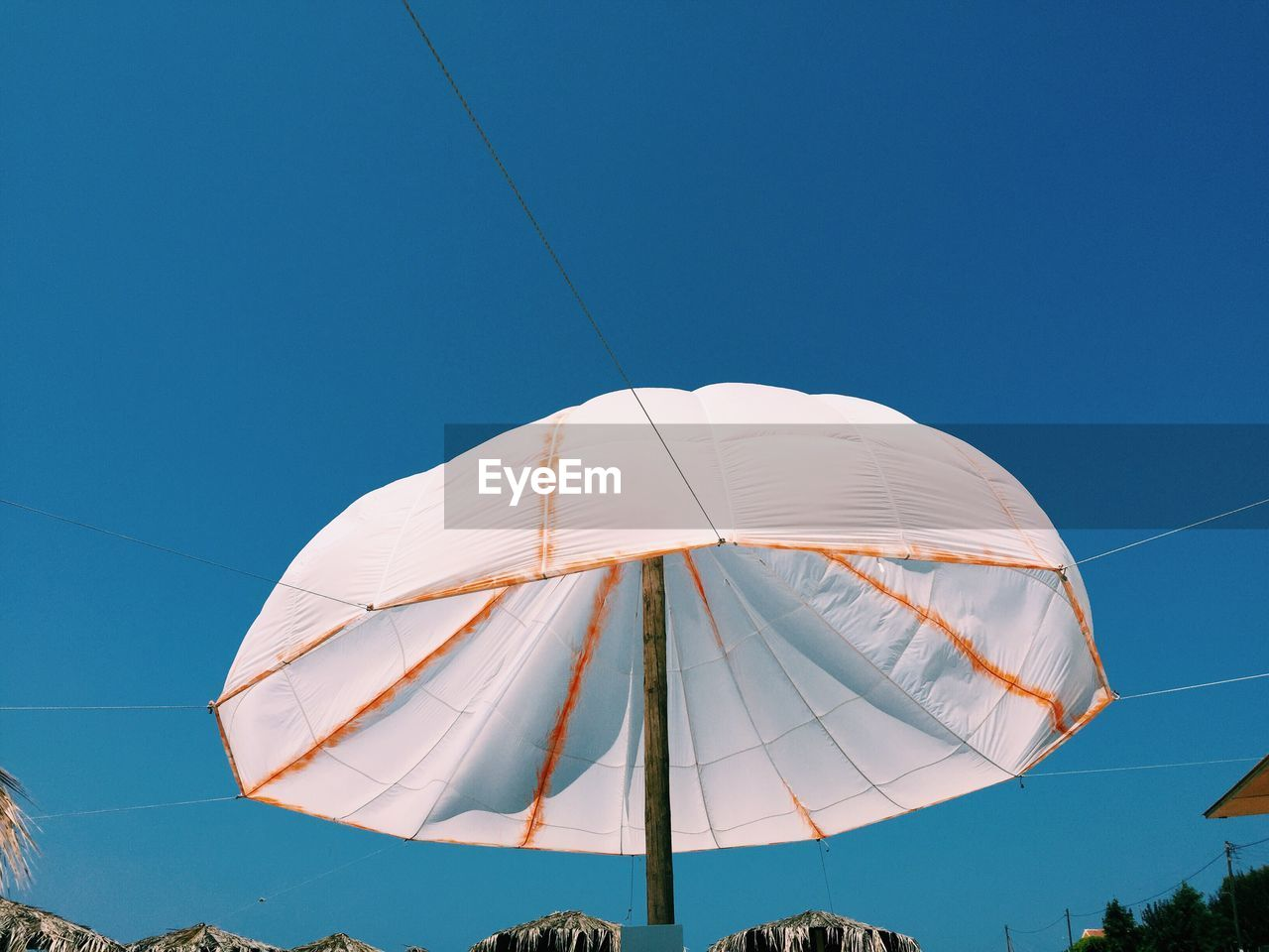 Low Angle View Of White Parasol Against Clear Blue Sky