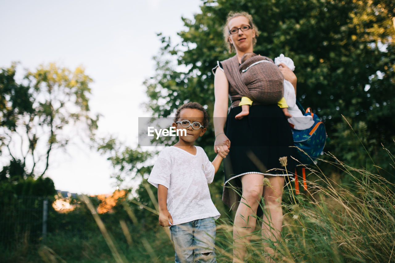 Portrait of mother with children standing on field against trees