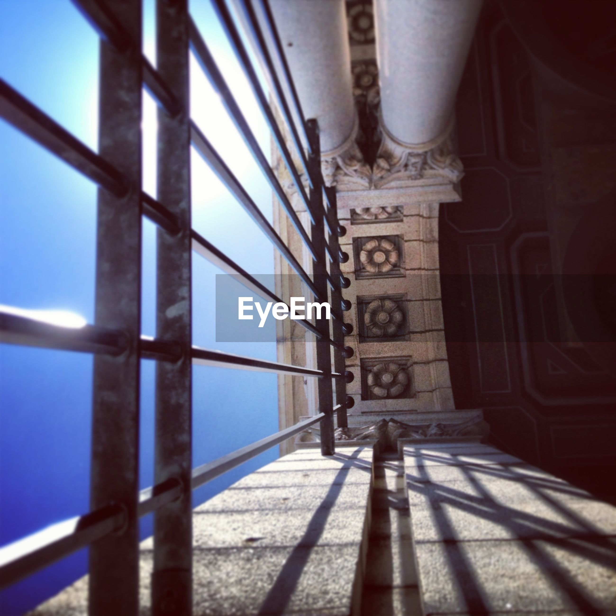 metal, low angle view, built structure, architecture, blue, connection, metallic, indoors, railing, no people, day, clear sky, sunlight, sky, part of, engineering, transportation, safety, close-up