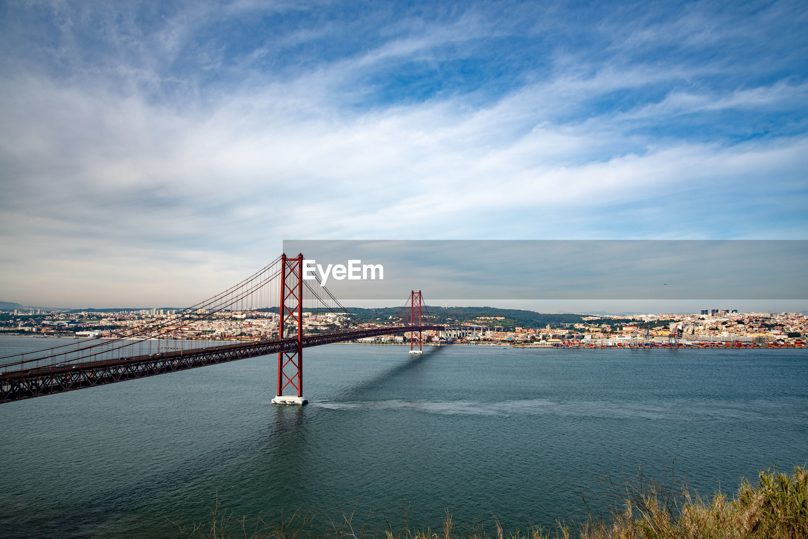 VIEW OF SUSPENSION BRIDGE IN CITY AT WATERFRONT