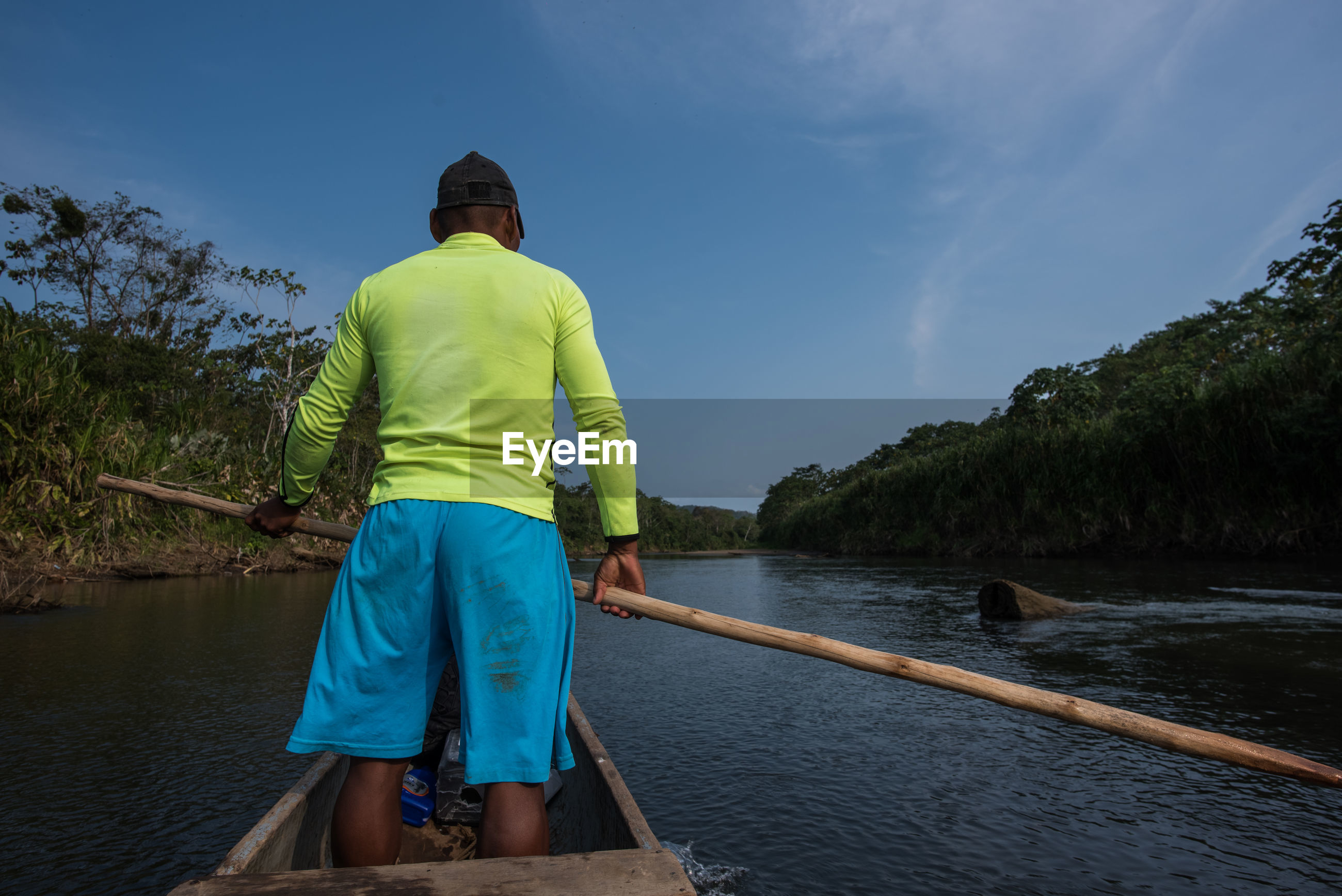 REAR VIEW OF MAN STANDING AT RIVERBANK AGAINST SKY