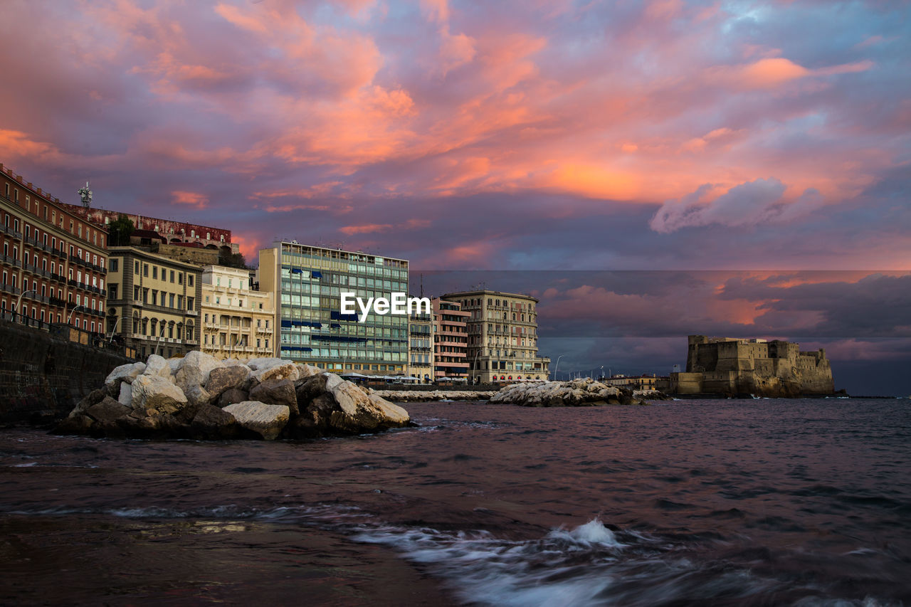 sky, cloud - sky, water, building exterior, built structure, architecture, sunset, sea, waterfront, nature, rock, solid, rock - object, motion, no people, city, building, beauty in nature, wave, outdoors, flowing water