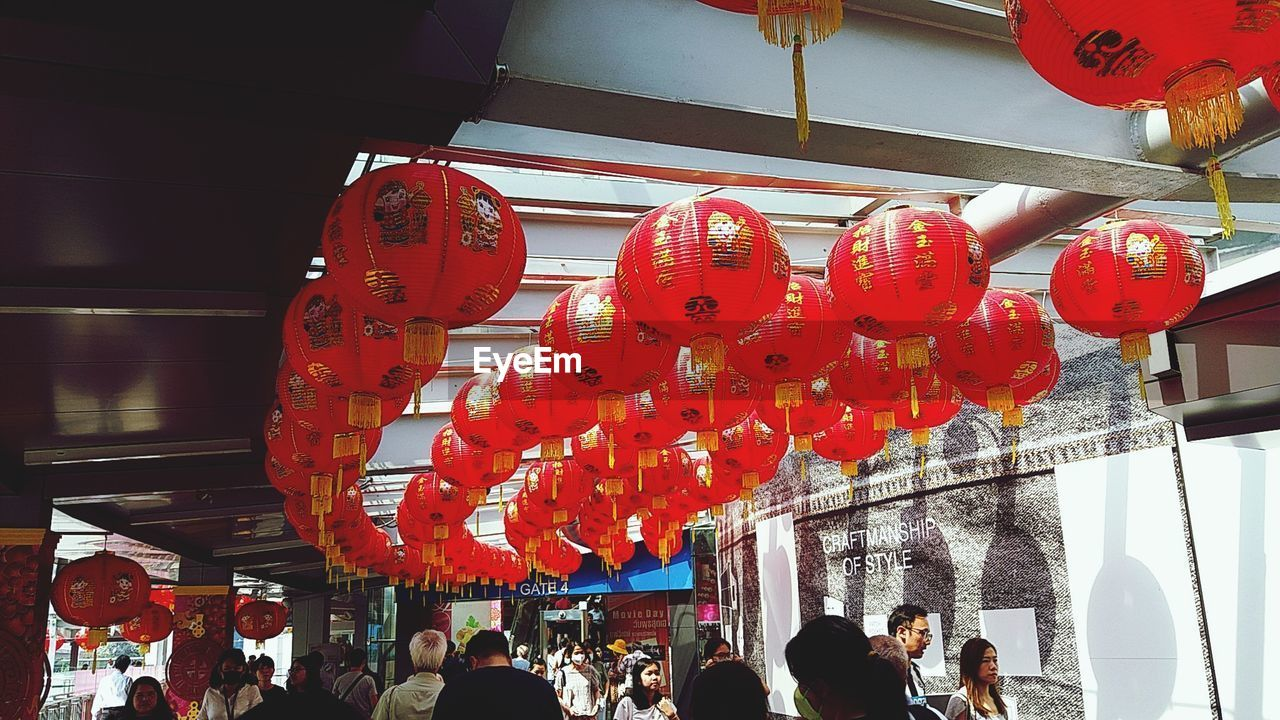 lantern, lighting equipment, chinese lantern, hanging, group of people, decoration, architecture, built structure, celebration, chinese new year, crowd, red, large group of people, building exterior, text, women, event, festival, chinese lantern festival, paper lantern