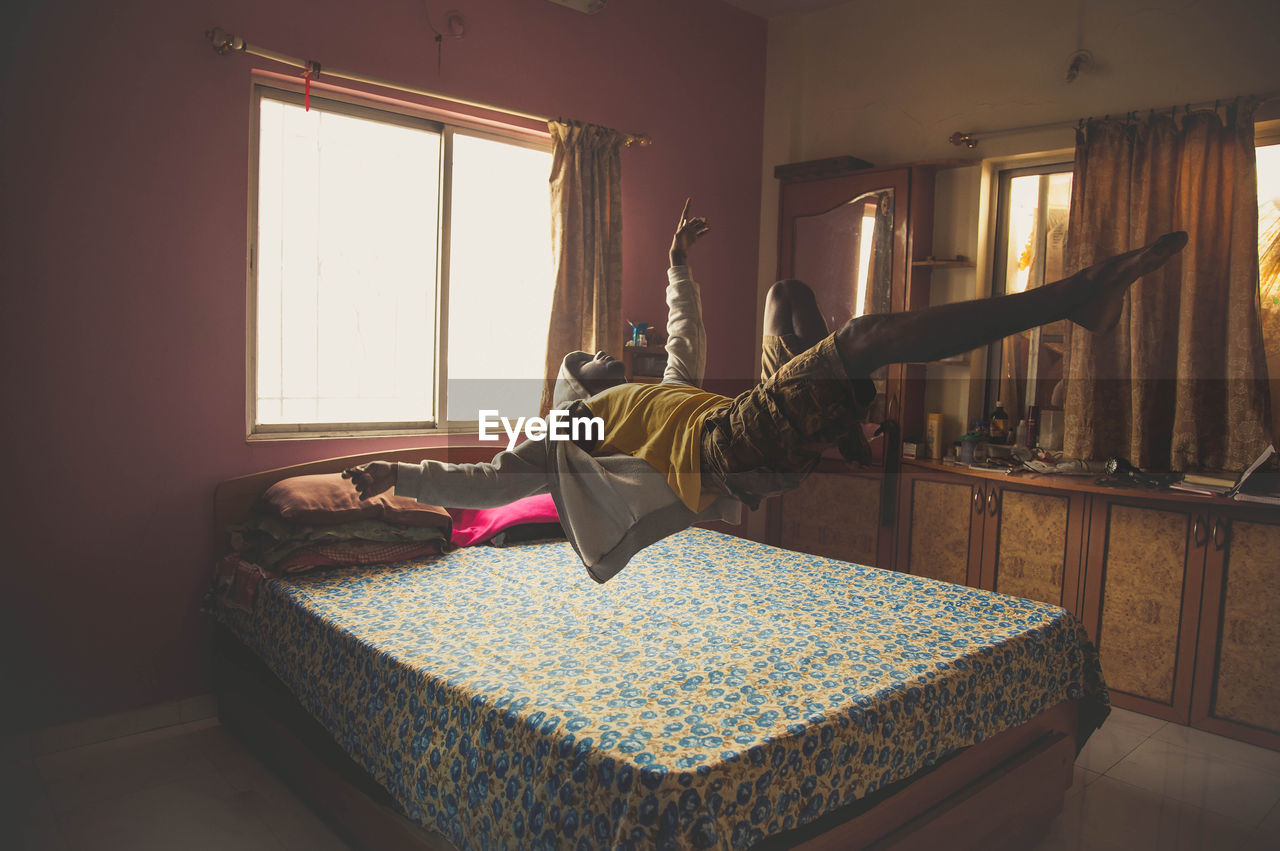 Full length of man levitating on bed at home