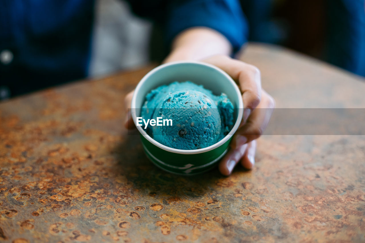 Close-Up Of Person Holding Ice Cream Cup On Rusty Metallic Table At Cafe