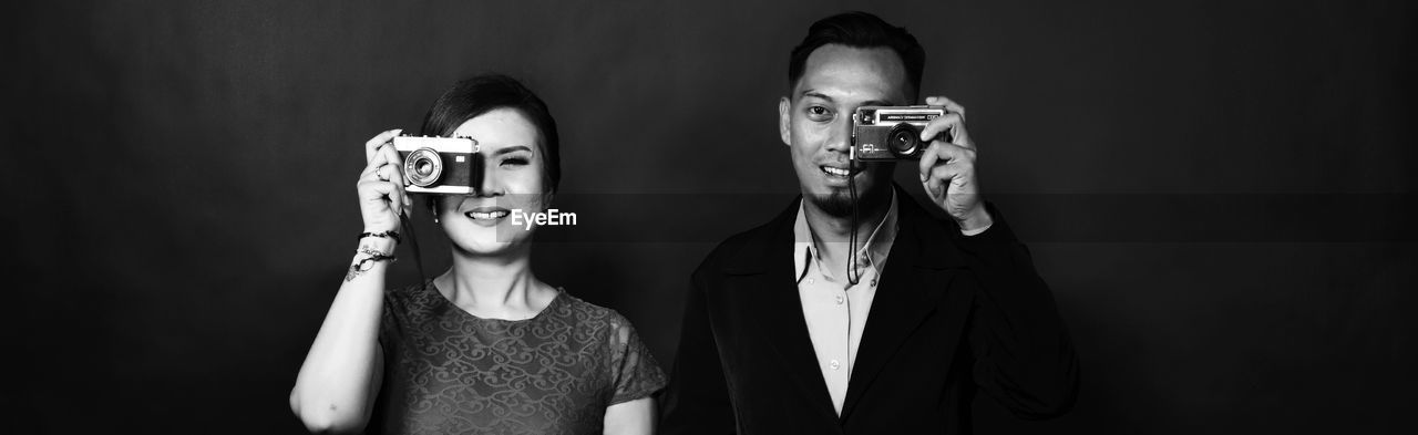 Portrait Of Smiling Man And Woman Holding Old Cameras Against Black Background