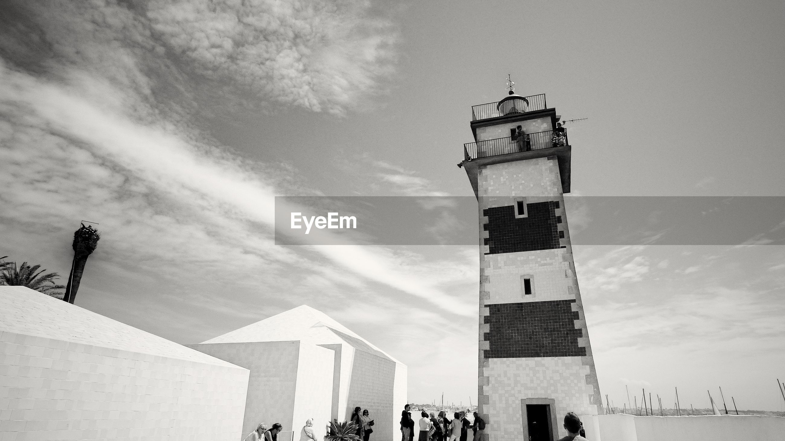People standing by lighthouse against sky