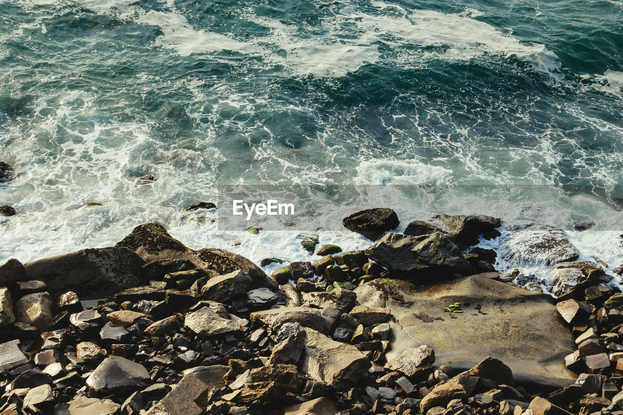 sea, water, beach, rock, solid, rock - object, land, motion, wave, nature, beauty in nature, day, no people, sport, aquatic sport, high angle view, outdoors, stone - object, pebble, rocky coastline, breaking, shallow