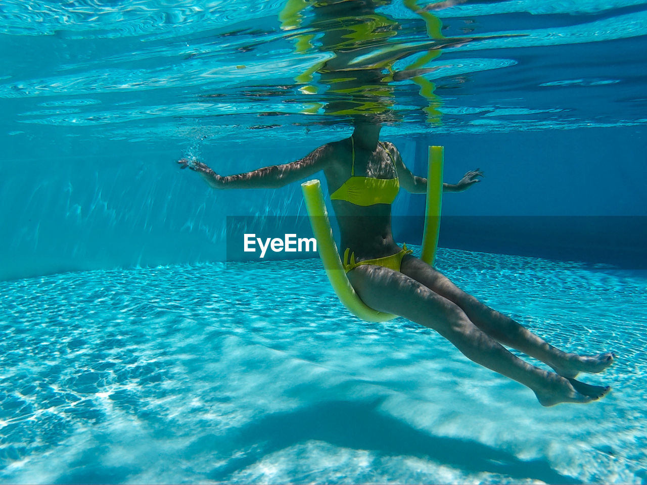 Underwater View Of Woman Sitting On Swimming Noodle