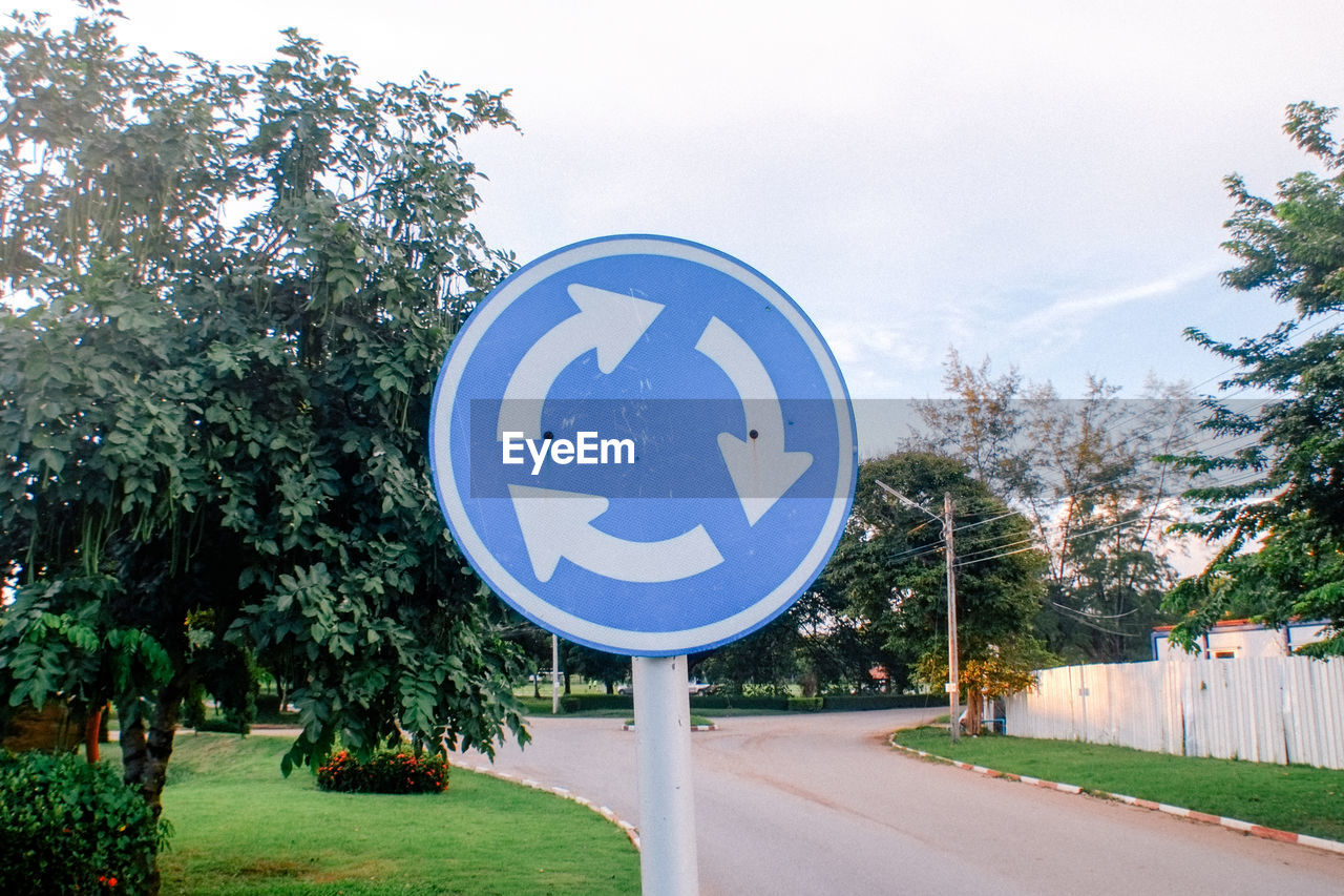 tree, plant, road, sign, communication, no people, direction, road sign, nature, day, shape, sky, transportation, symbol, guidance, architecture, blue, city, circle, built structure, outdoors