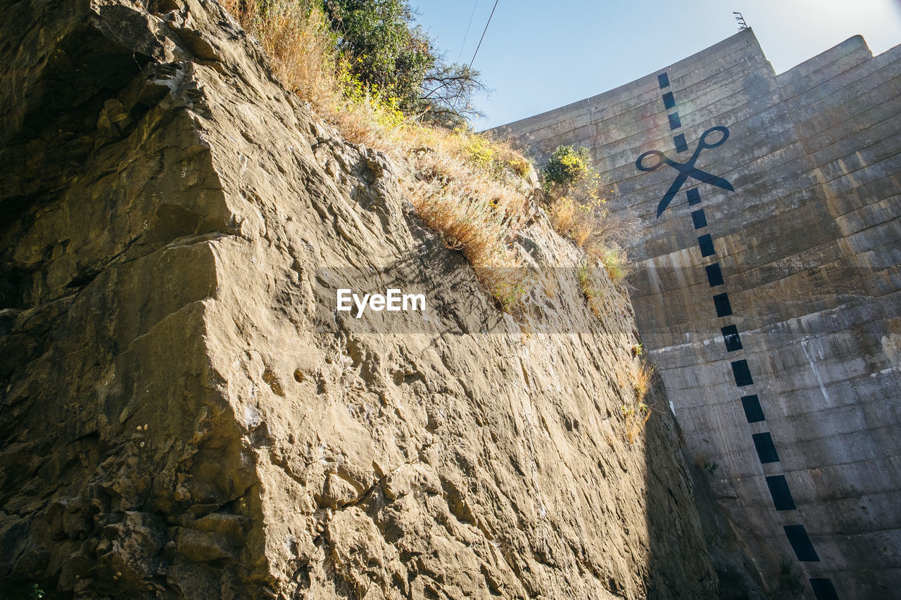 LOW ANGLE VIEW OF CROSS ON ROCK AGAINST WALL