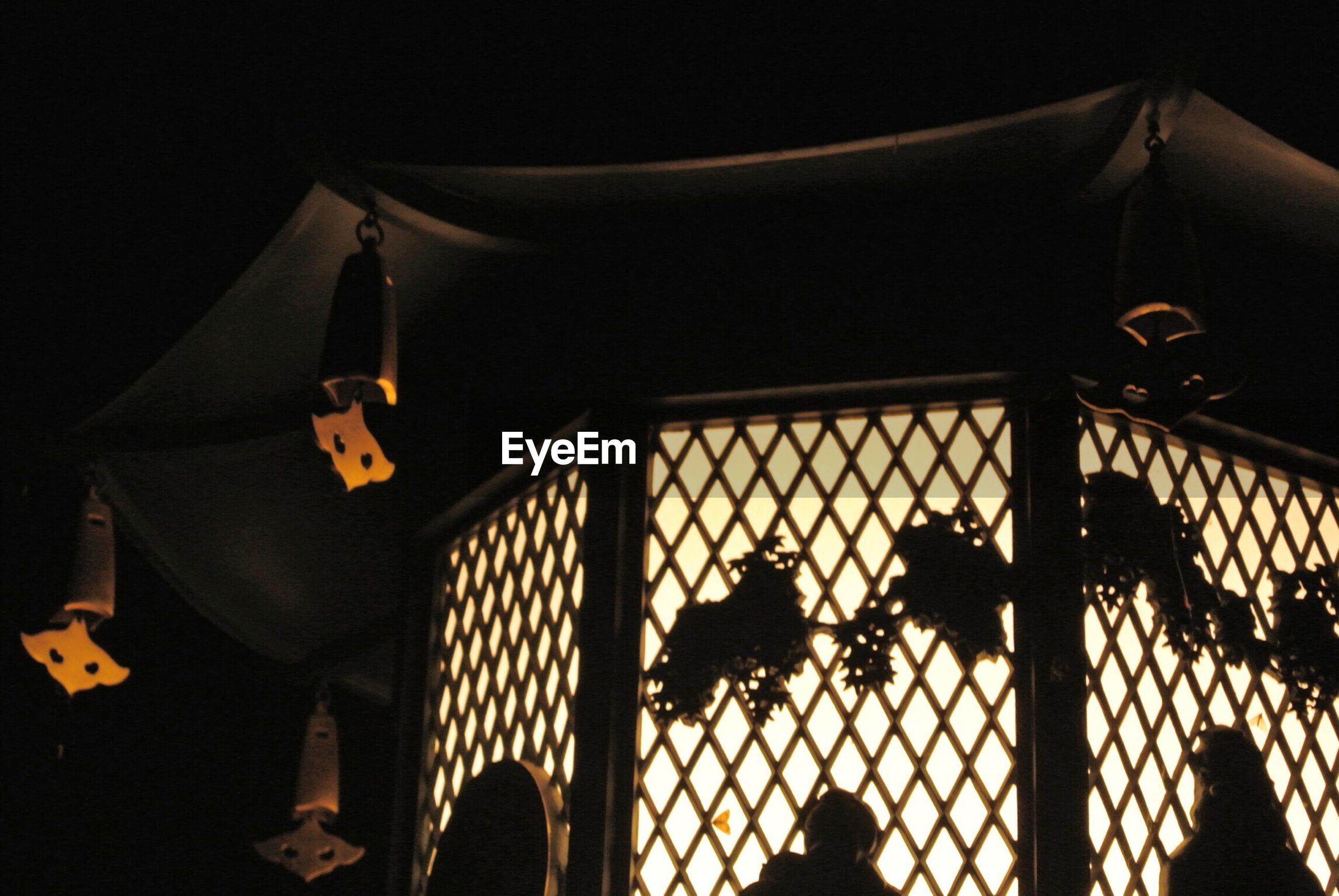 Silhouette of hanging objects from illuminated structure