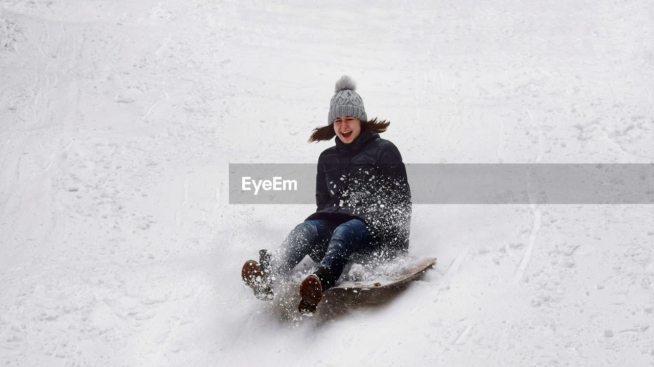 Full length of woman sledding on snow covered field