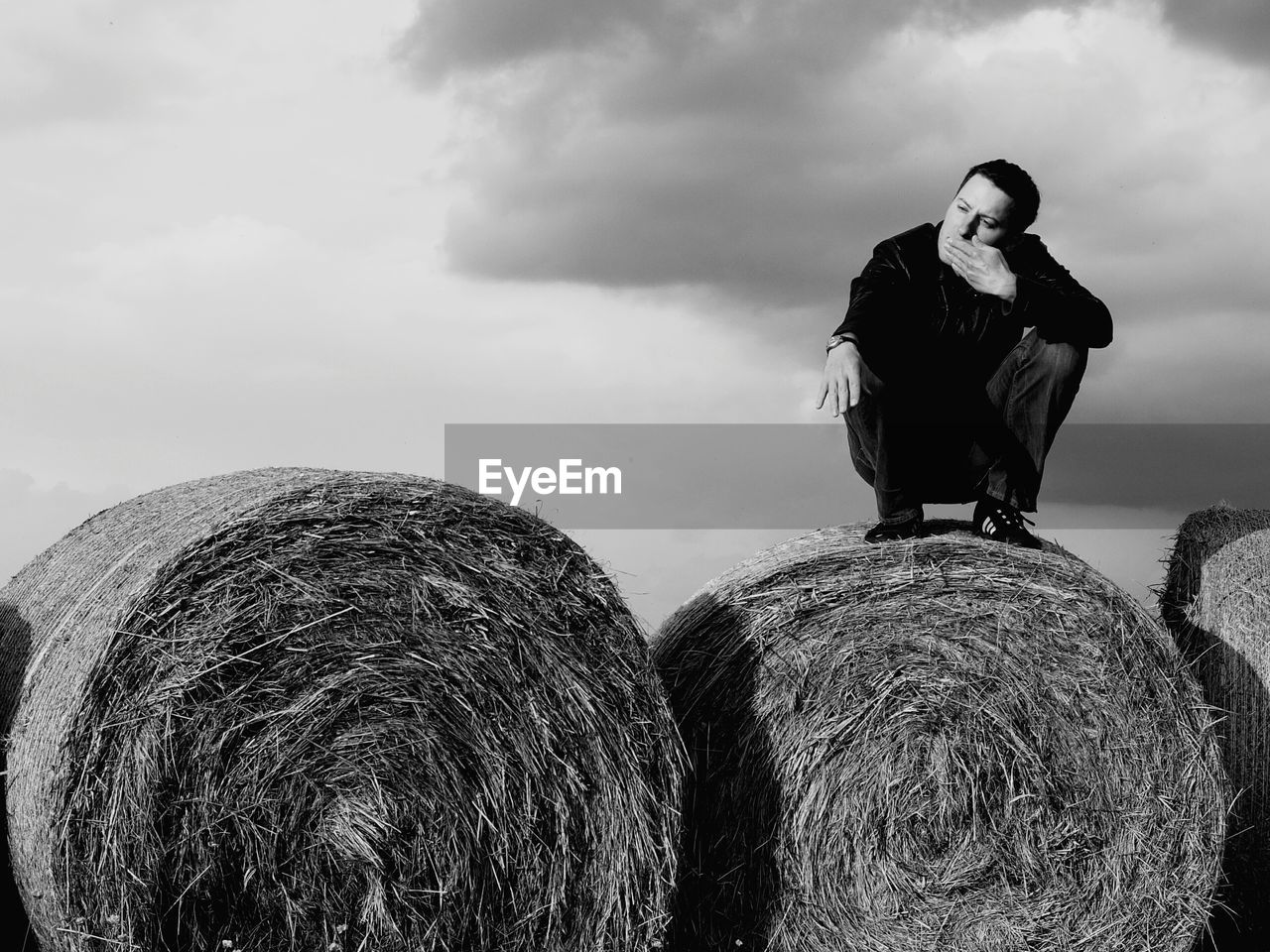 Full Length Of Man Crouching On Hay Bale Against Cloudy Sky