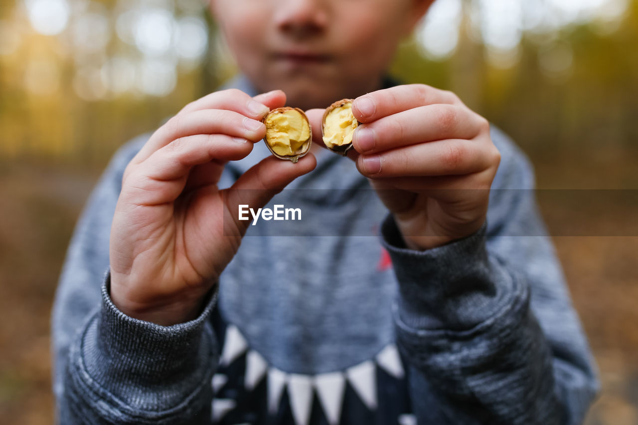 Midsection of boy holding nut while standing outdoors