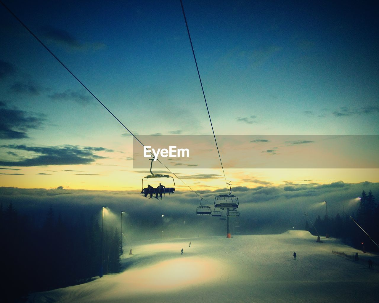 Ski lift over snow covered field against sky during sunset