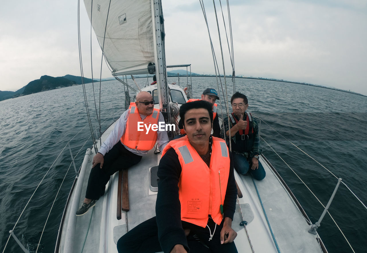 nautical vessel, water, sea, sky, transportation, mode of transportation, real people, looking at camera, nature, lifestyles, cloud - sky, portrait, men, day, people, sailing, sitting, leisure activity, togetherness, outdoors, sailboat