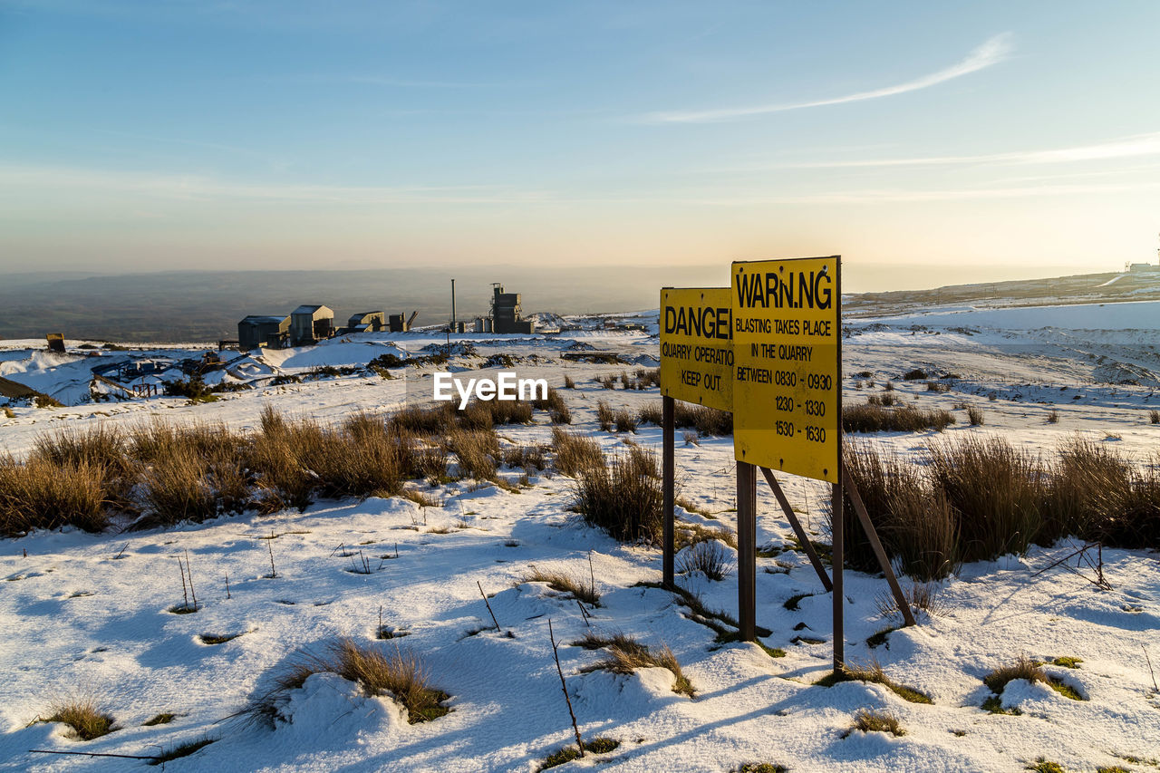 Yellow Warning Signs On Snow Covered Field Against Sky