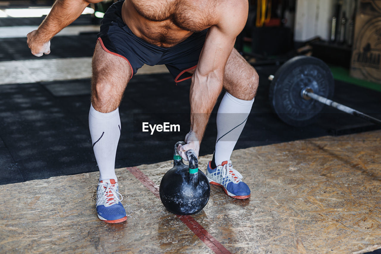 Low Section Of Man Lifting Kettlebell While Exercising In Gym
