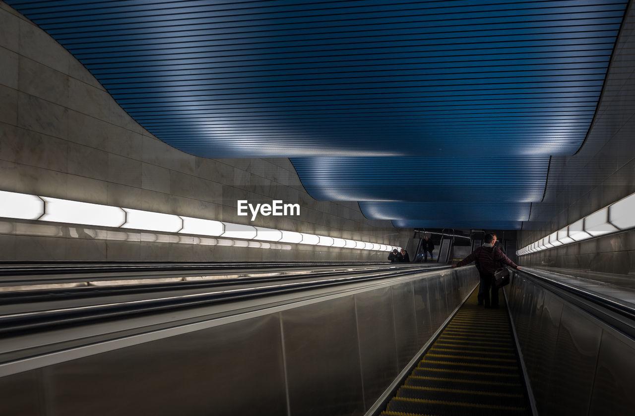 Man Walking On Escalator At Railroad Station