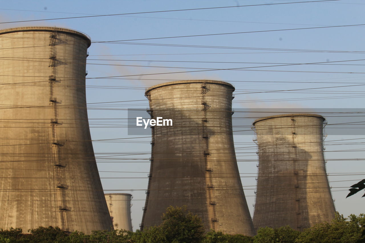 LOW ANGLE VIEW OF SMOKE STACK AGAINST FACTORY