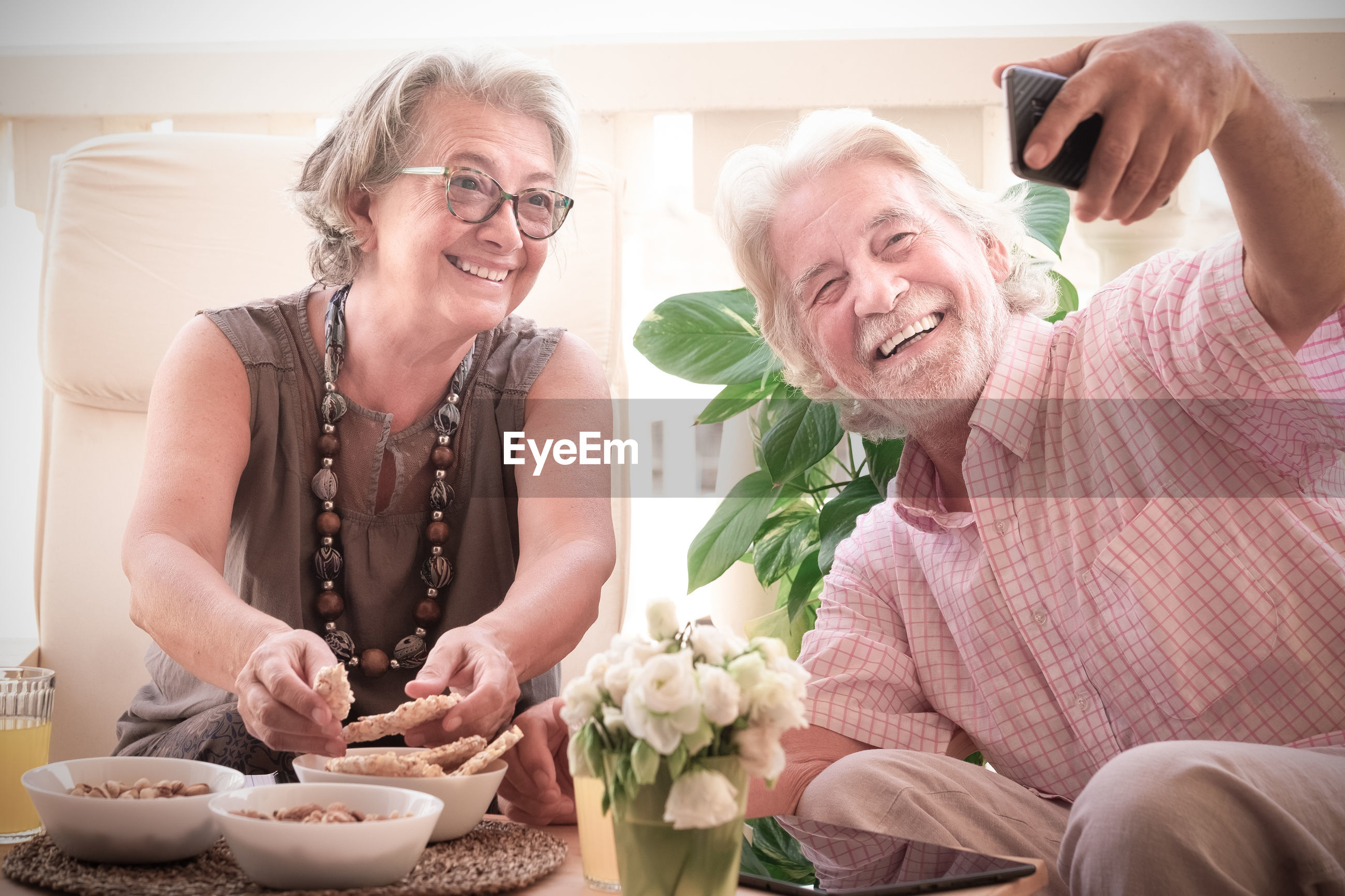 Smiling couple eating food while taking selfie by mobile phone on table