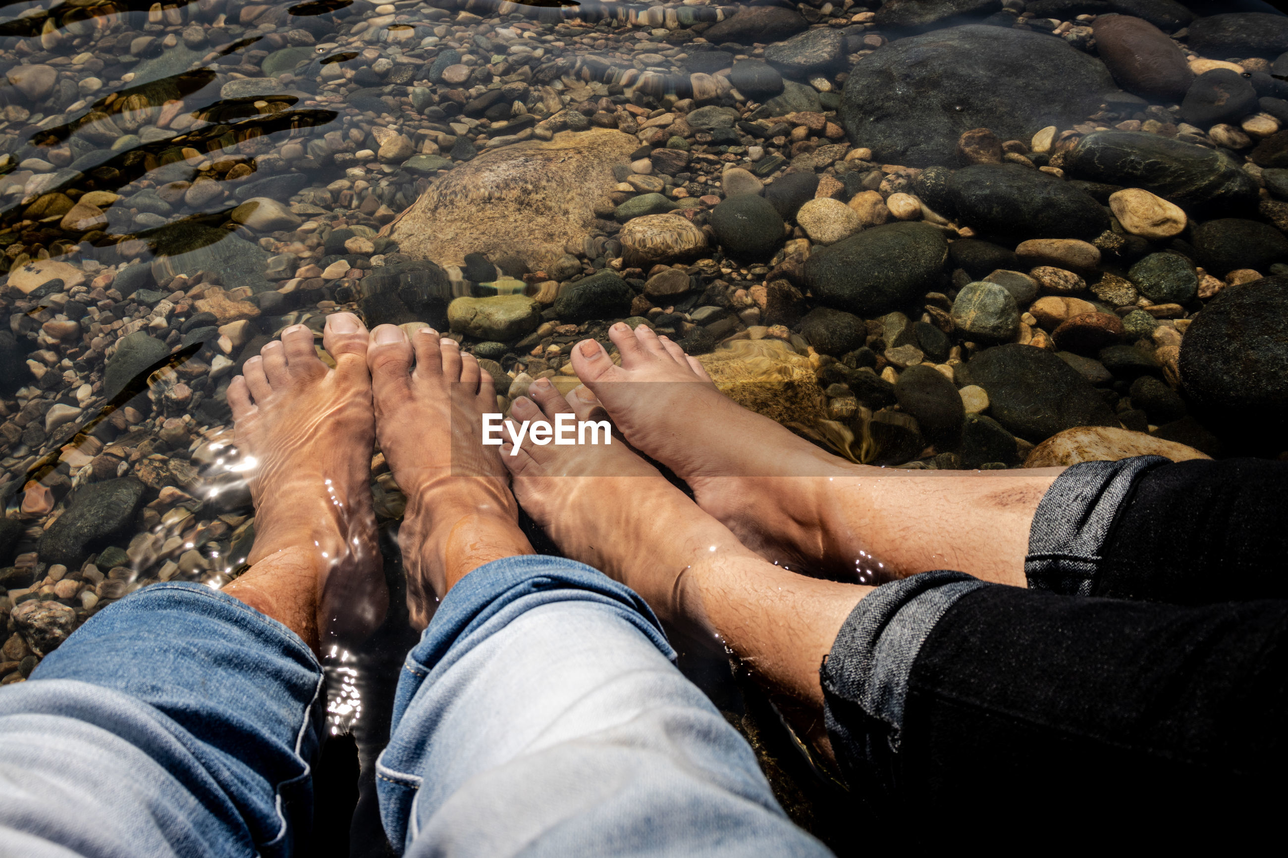Low section of couple sitting in river
