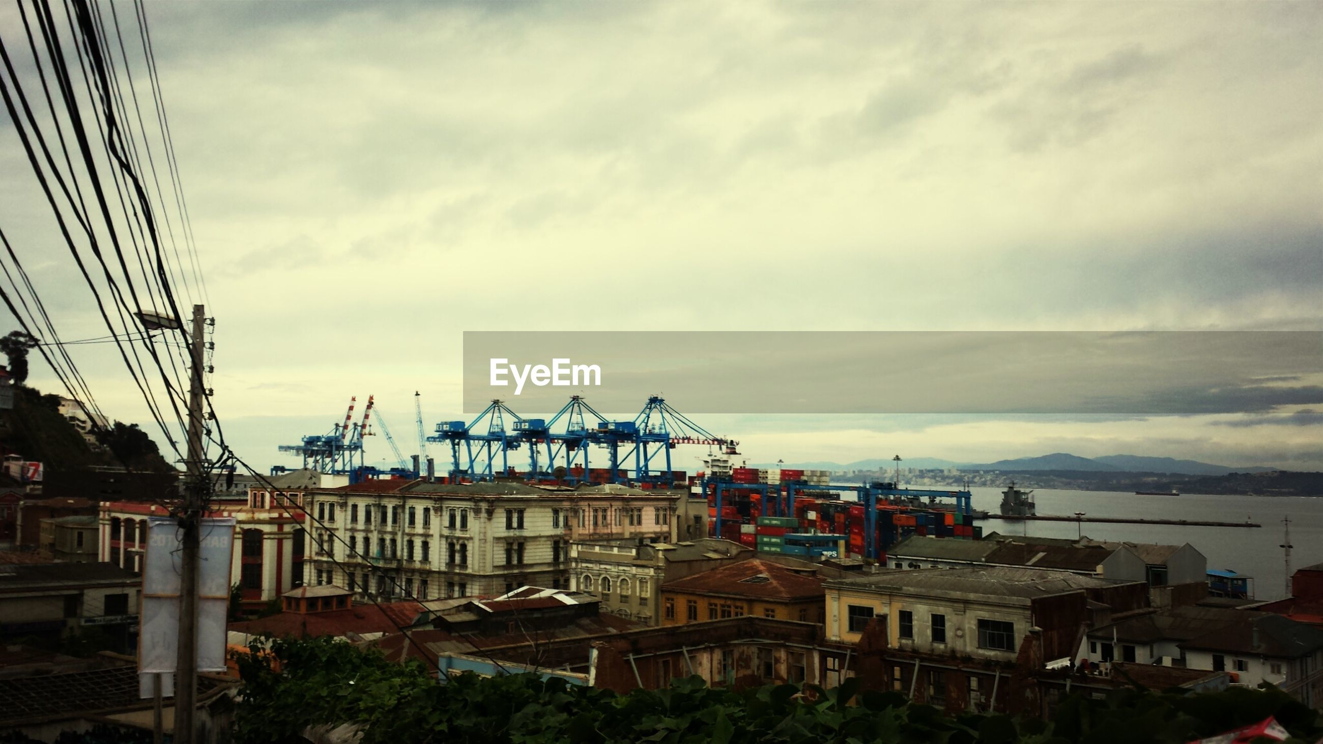 building exterior, architecture, built structure, sky, cloud - sky, cloudy, city, residential building, residential structure, house, residential district, cloud, crane - construction machinery, water, harbor, town, outdoors, cityscape, day, building