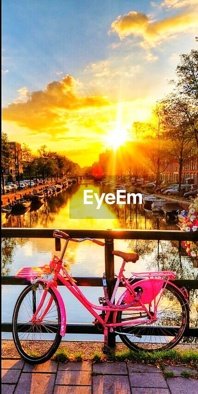 bicycle, sunset, transportation, sunlight, mode of transport, outdoors, sky, no people, land vehicle, stationary, nature, water, tree, scenics, beauty in nature, day