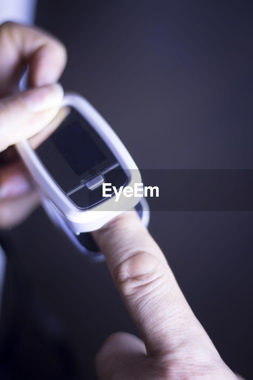 Close-up of medical equipment on finger