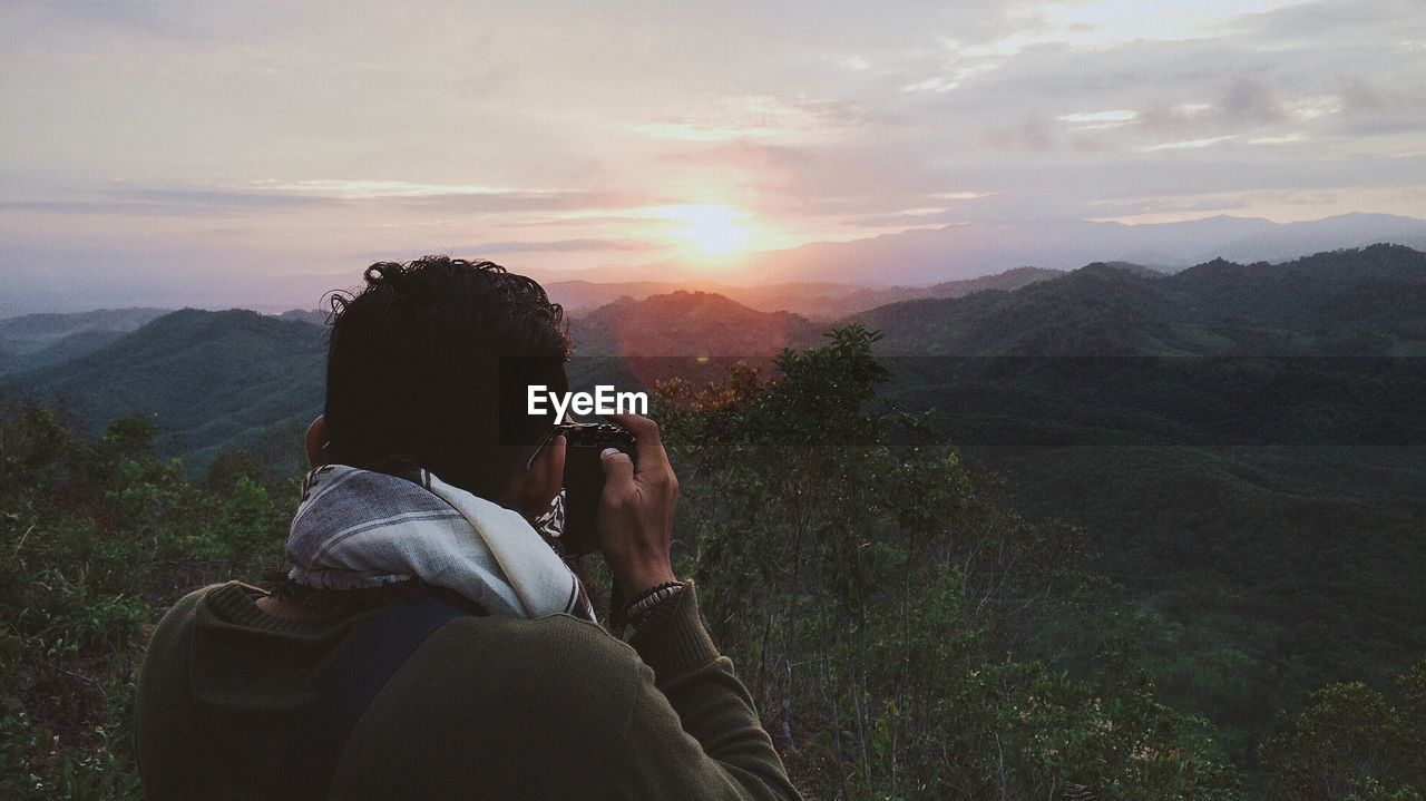 Rear view of man photographing green mountains during sunrise