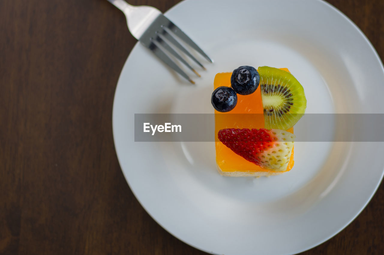 food, food and drink, fruit, plate, healthy eating, table, still life, freshness, wellbeing, indoors, kitchen utensil, fork, ready-to-eat, slice, eating utensil, directly above, berry fruit, wood - material, no people, close-up, temptation, orange, breakfast, fruit salad