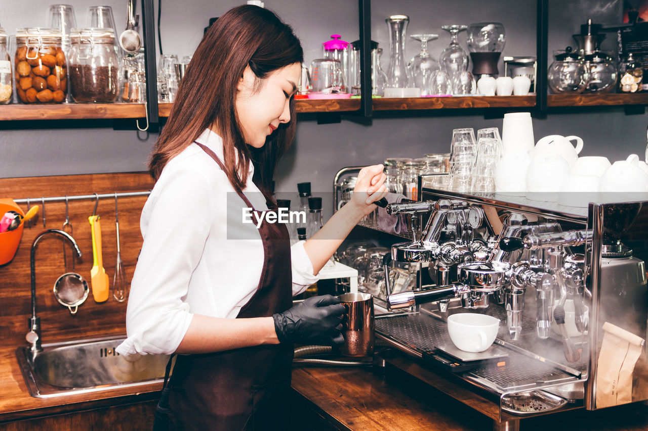 food and drink, one person, young adult, indoors, occupation, women, drink, standing, real people, business, adult, young women, waist up, working, container, holding, hairstyle, bar - drink establishment, bar counter, refreshment, preparation, coffee maker, barista, bartender, glass