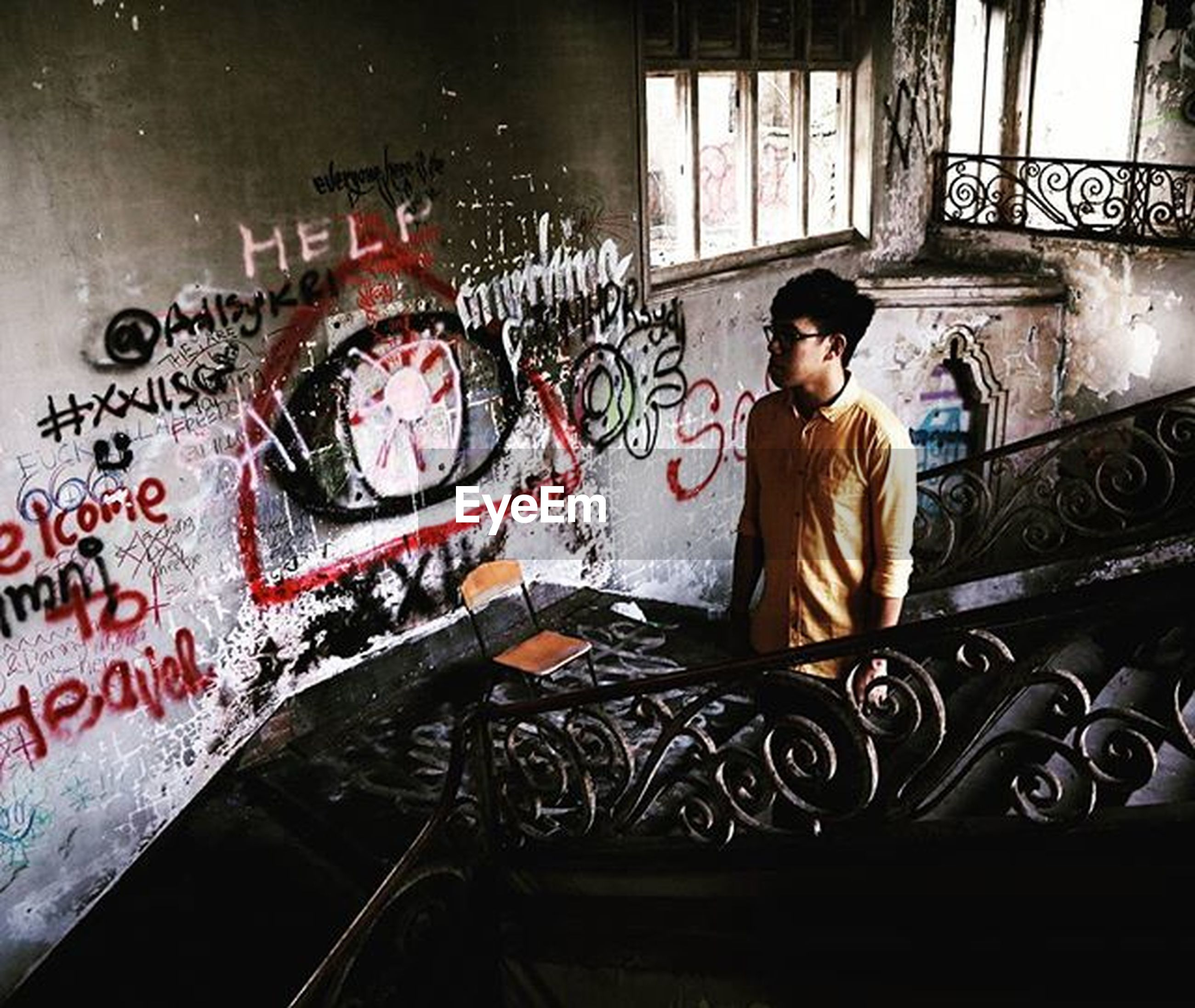 indoors, lifestyles, text, casual clothing, communication, leisure activity, graffiti, men, transportation, young men, mode of transport, wall - building feature, standing, technology, person, western script, architecture, built structure