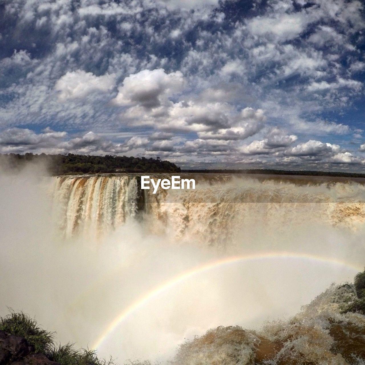 Waterfall And Rainbow Against Sky