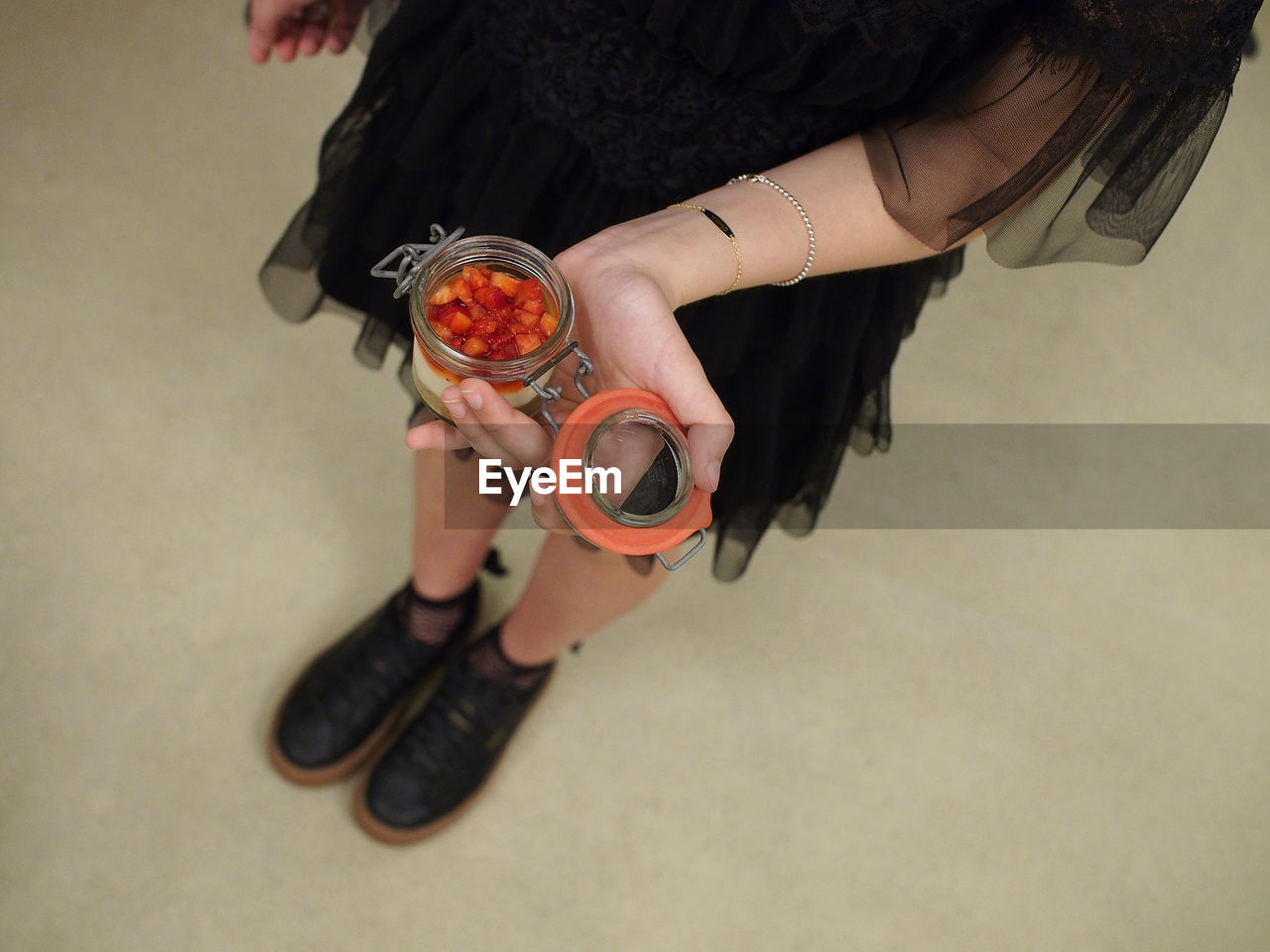 Low section of woman holding food in container