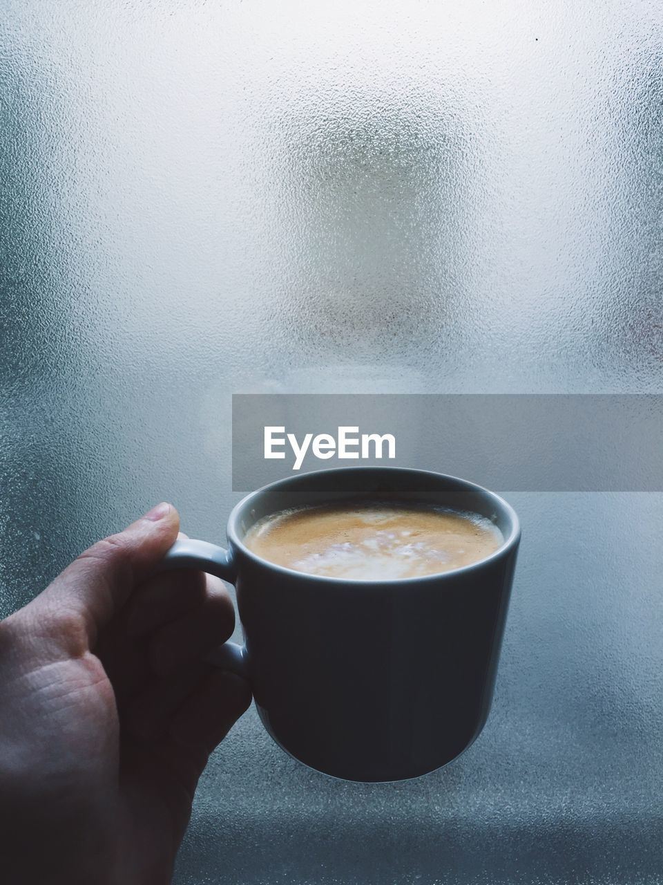 Cropped Image Of Hand Holding Coffee Cup Against Frosted Glass