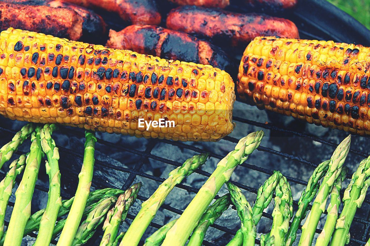 food, food and drink, freshness, close-up, healthy eating, wellbeing, vegetable, barbecue, no people, barbecue grill, day, grilled, green color, nature, still life, corn, plant, focus on foreground, outdoors, high angle view, sweetcorn