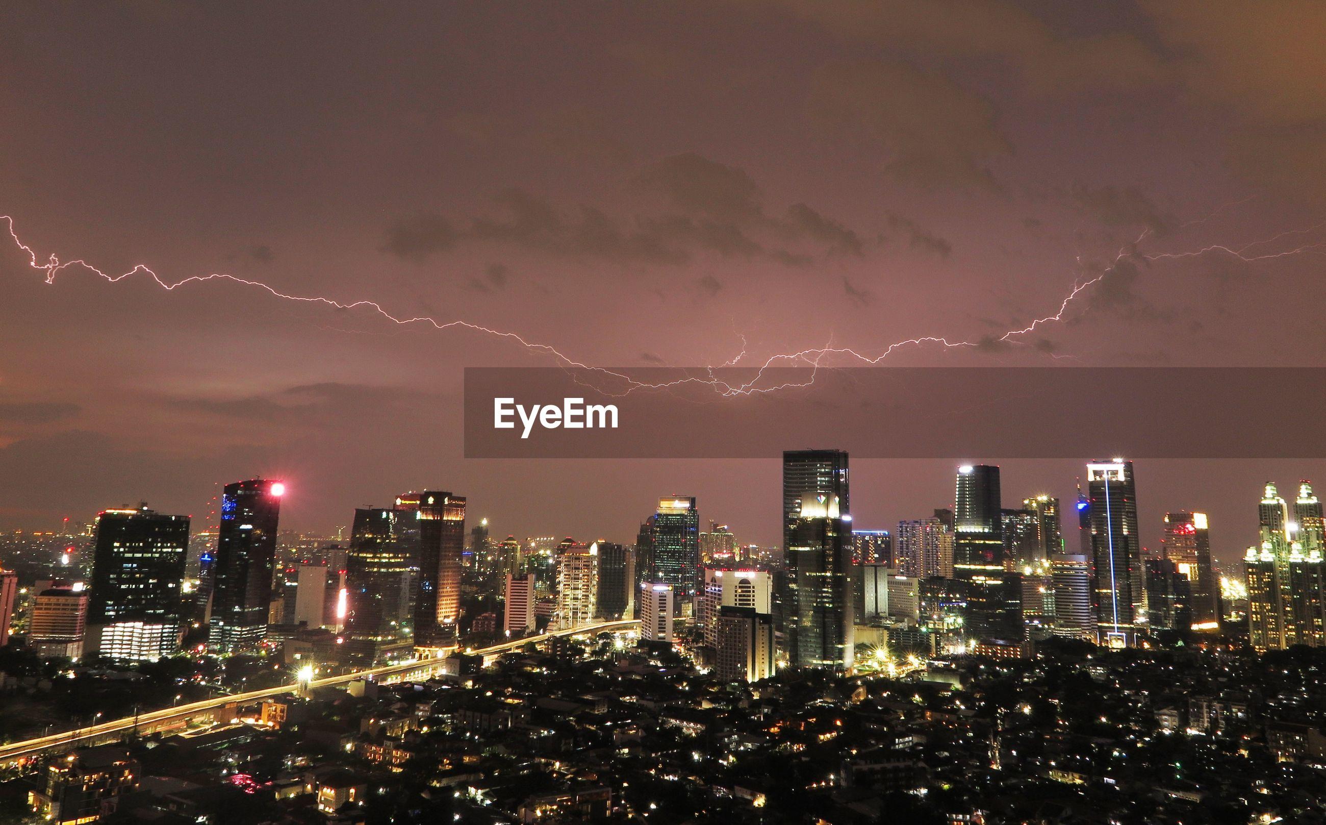 View of lightning over illuminated city at dusk