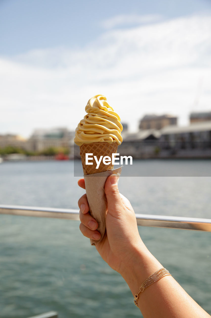 sweet, sweet food, human hand, ice cream, hand, frozen food, dessert, human body part, dairy product, indulgence, frozen, ice cream cone, one person, holding, cone, temptation, real people, food, food and drink, water, body part, outdoors, finger