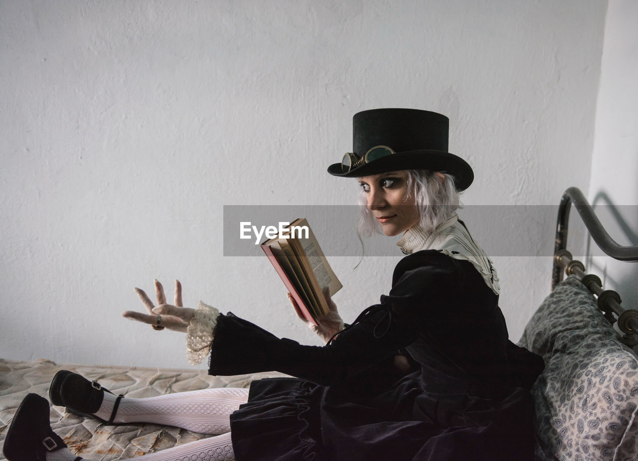 Thoughtful woman wearing costume while reading book on bed at home