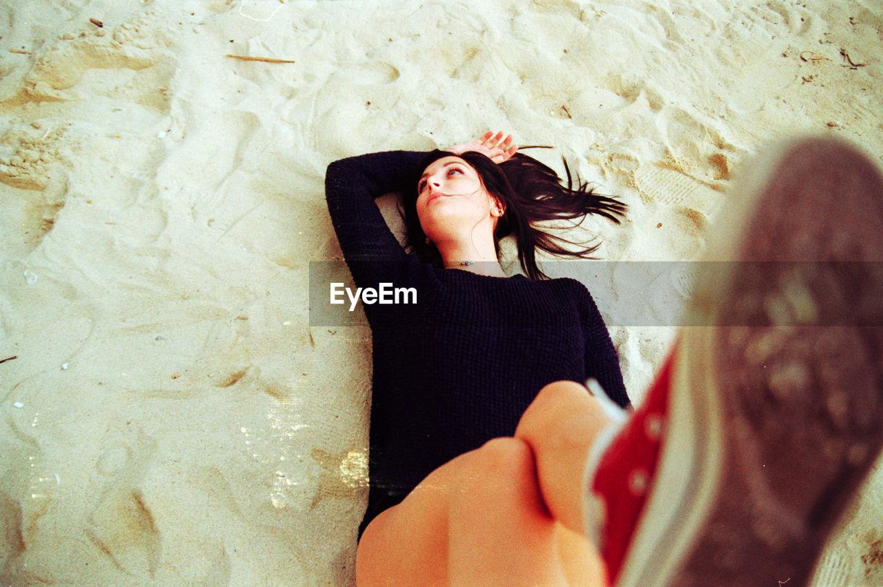 High angle view of young woman lying on sandy beach