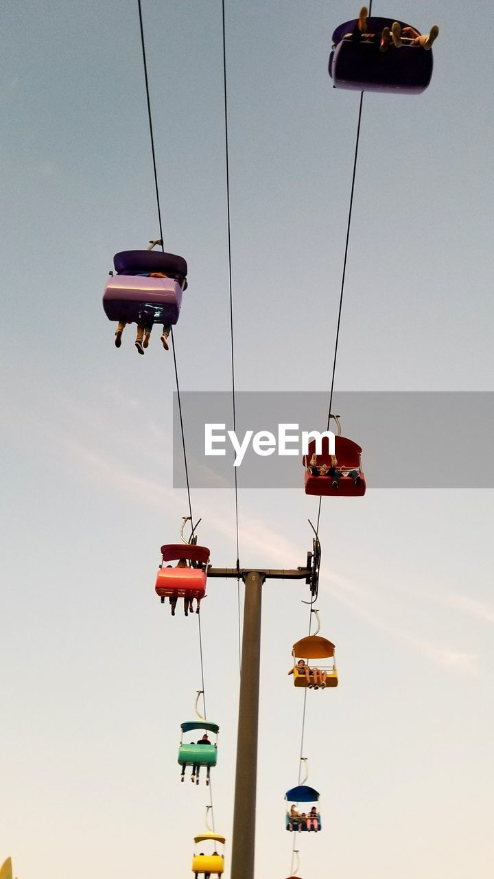 Low Angle View Of People Sitting In Ski Lift Against Sky