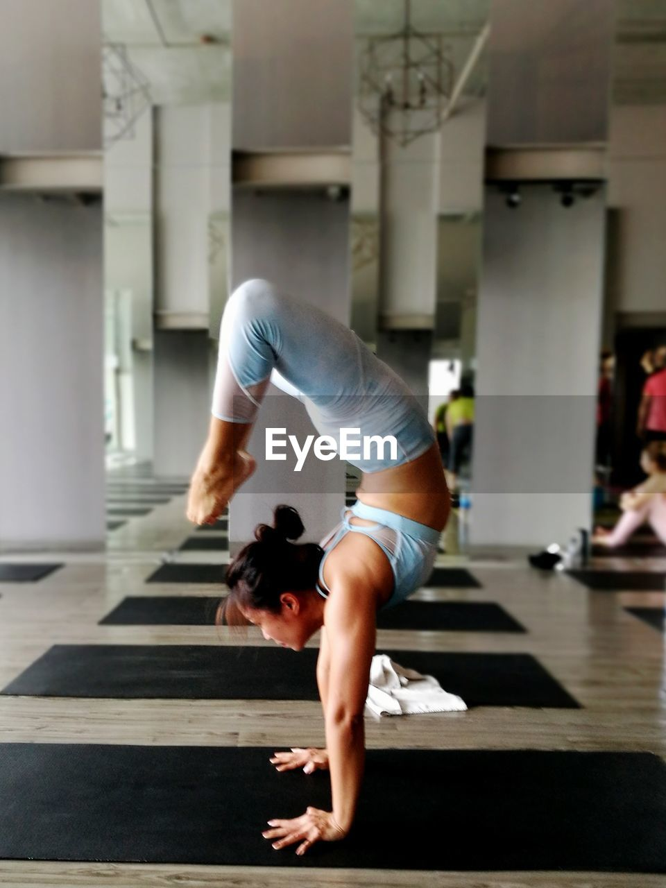 Full Length Of Woman Practicing Handstand At Health Club