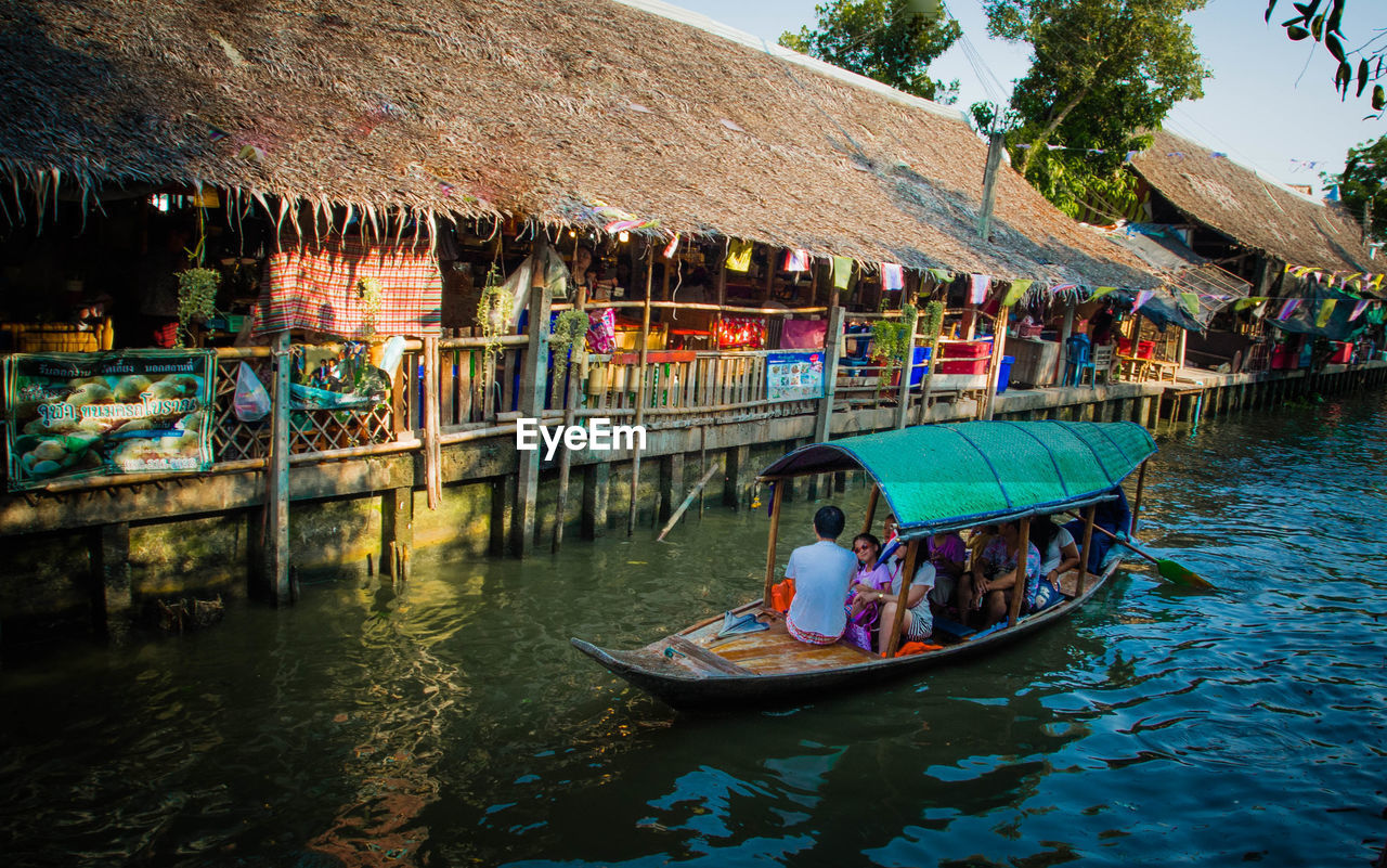 water, nautical vessel, real people, transportation, boat, outdoors, waterfront, mode of transport, men, leisure activity, day, built structure, building exterior, architecture, lifestyles, sitting, women, rowing, oar, nature, adult, people