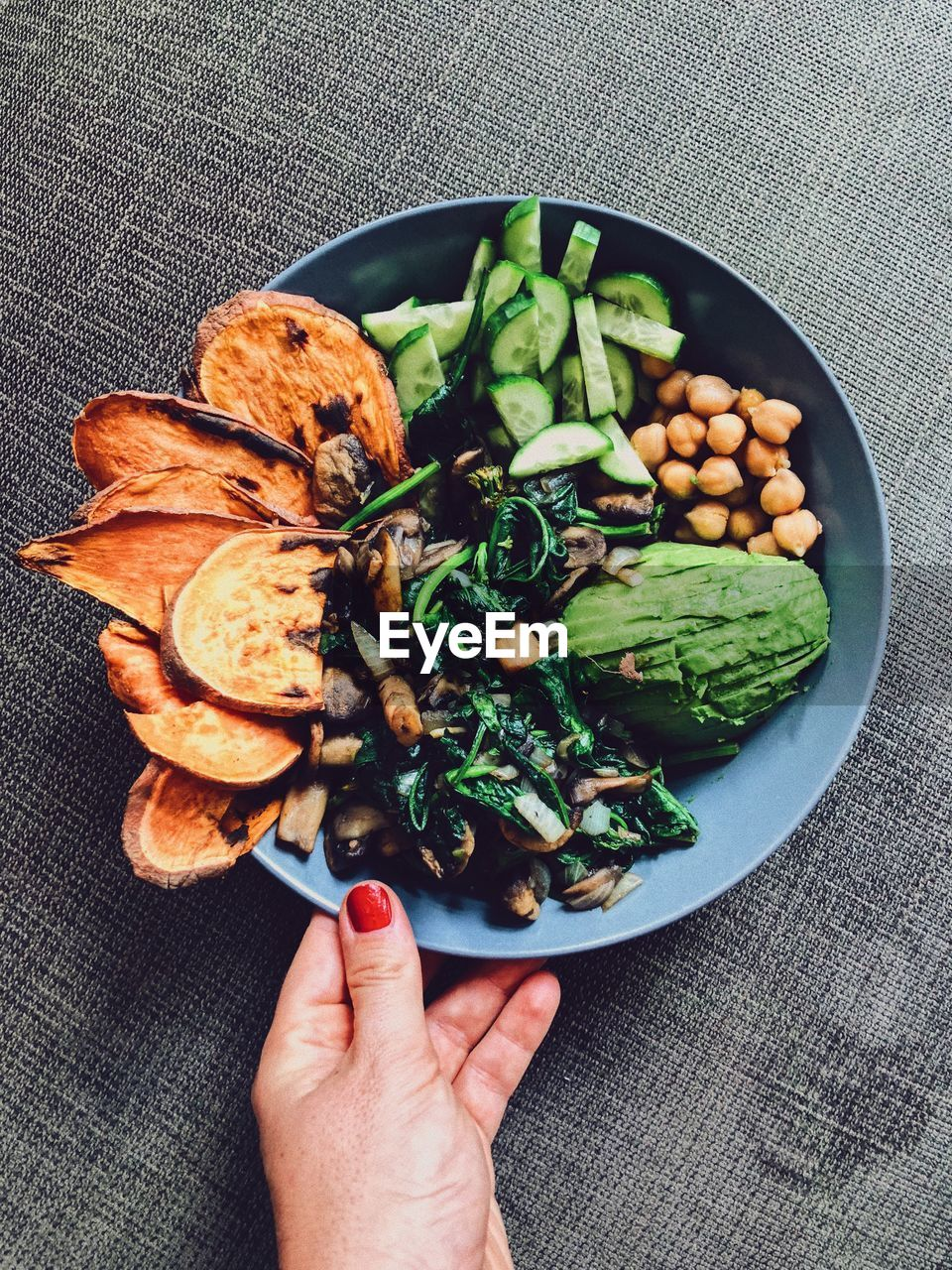 food, human hand, hand, food and drink, healthy eating, vegetable, human body part, wellbeing, freshness, one person, ready-to-eat, indoors, directly above, unrecognizable person, high angle view, holding, bowl, real people, personal perspective, body part, finger